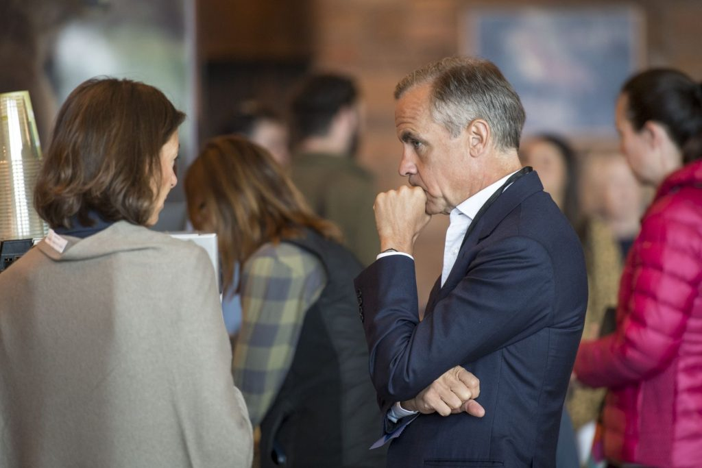 Mark Carney stands pensively in dark suit while listening to woman speak at economic  symposium